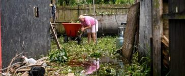 Joan Markel, stands in food waters cleaning debris from her yard, after Hurricane Irma near Jerome