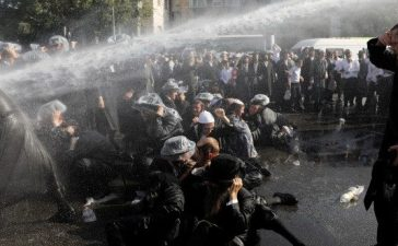 Israeli ultra-Orthodox Jewish men are sprayed with water during clashes with police at a protest against the detention of a member of their community who refuses to serve in the Israeli army, in Jerusalem September 17, 2017 REUTERS/Ronen Zvulun
