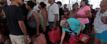 FILE PHOTO: People line up to buy gasoline at a gas station after the area was hit by Hurricane Maria, in San Juan