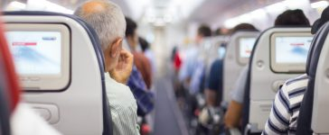 Interior of airplane with passengers on seats waiting to take off. Matej Kastelic (Shutterstock)
