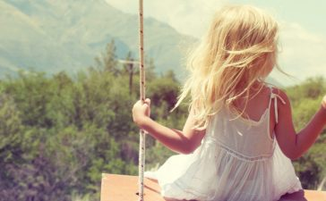 Little girl having fun on a swing outdoor MorganStudio (Shutterstock)