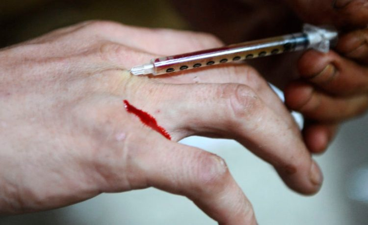 A man injects heroin into a vein in his hand. August 3, 2009. REUTERS/Bor Slana