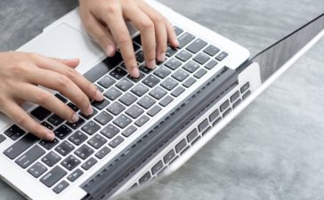 Close up hands of an employee is using a computer notebook by typing on keyboard at the desk (Shutterstock/Surapong Buacharoen)