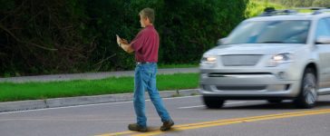 A man distracted by his cellphone walks across a busy street. [Shutterstock - Mike Focus]