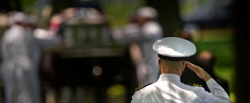 ARLINGTON, Va. (May 2, 2013) An officer salutes as members of the U.S. Navy Ceremonial Guard take the casket of a Sailor killed during the Vietnam War to his gravesite at Arlington National Cemetery. Lt. Dennis Peterson, from Huntington Park, Calif.; Ensign Donald Frye, from Los Angeles; and Aviation Antisubmarine Warfare Technicians 2nd Class William Jackson, from Stockdale, Texas, and Donald McGrane, from Waverly, Iowa, all four assigned to Helicopter Squadron (HS) 2, were killed when their SH-3A Sea King helicopter was shot down July 19, 1967 over Ha Nam Province, North Vietnam. (U.S. Navy photo by Mass Communication Specialist 2nd Class Todd Frantom/Released)