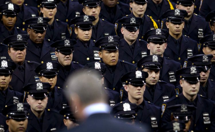 New York Mayor Bill de Blasio speaks from the podium to the New York City Police Academy Graduating class in New York December 29, 2014. Hundreds of officers took part in the ceremony at Madison Square Garden. REUTERS/Carlo Allegri