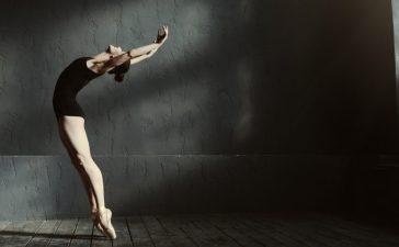Flexible ballet dancer stretching in the dark lighted studio Shutterstock/ YAKOBCHUK VIACHESLAV