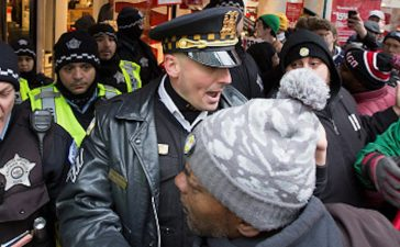 CHICAGO, IL - NOVEMBER 25: Chicago Police work to control about 400 anti-Black Friday protesters on Michigan Avenue on November 25, 2016 in Chicago, Illinois. Protesters gathered along Chicago's Magnificant Mile to encourage a boycott of Black Friday shopping while calling for changes to the criminal justice system. (Photo by Tasos Katopodis/Getty Images)
