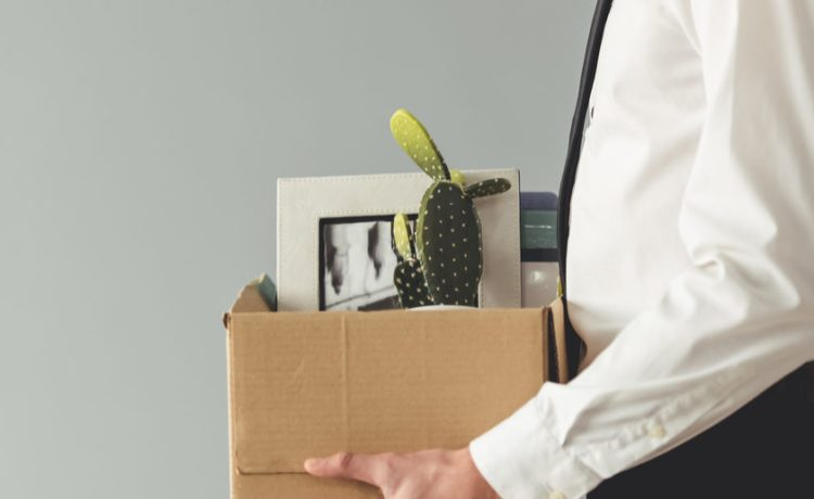 Getting fired. Cropped image of handsome businessman in formal wear holding a box with his stuff, on gray background (Shutterstock/George Rudy)
