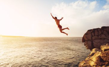 A man is jumping off a cliff. (Shutterstock/EpicStockMedia)