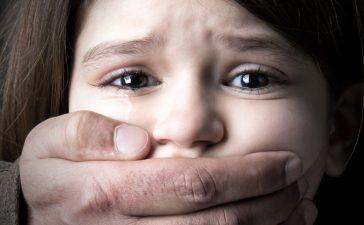 Man Silencing A Young Girl (shutterstock/Luis Louro)