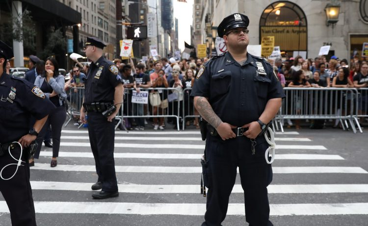 NYPD policemen stand guard as anti-Trump protesters gather in Manhattan in New York, U.S., August 14, 2017. REUTERS/Stephen Yang