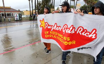 Local fast food workers take part in nationwide protests to denounce President-elect Donald Trump's nomination of Andy Puzder, a restaurant mogul who owns Carl's Jr. and other chains, as U.S. Secretary of Labor outside a Carl's Jr. restaurant in Los Angeles, California, U.S., January 12, 2017. REUTERS/Mike Blake