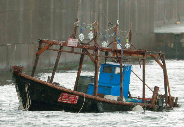 A wooden boat, which according to a police official carried eight men who said they were from North Korea and appear to be fishermen whose vessel ran into trouble, is seen near a breakwater in Yurihonjo, Akita Prefecture, Japan, November 24, 2017. Mandatory credit Kyodo/via REUTERS