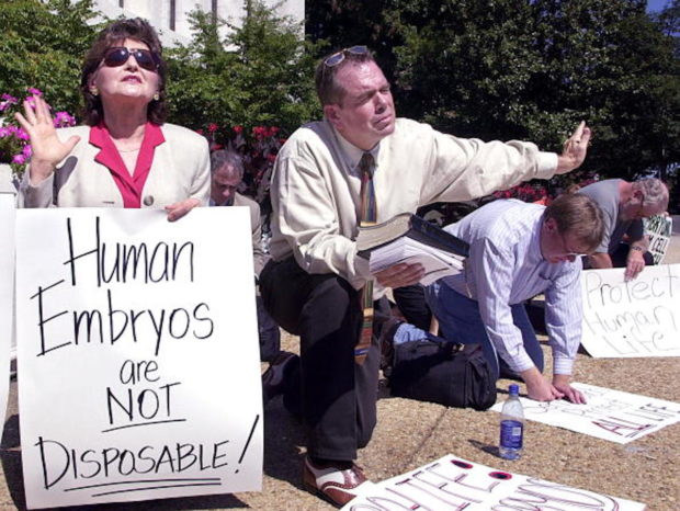 WASHINGTON, DC - SEPTEMBER 6: Rev. Flip Benham of Dallas, Texas, (C) a member of the Christian Defense Coalition prays with Eva Edl of Aiken, South Carolina (L) and Rev. Cal Zastro (R) as they gather in front of a senate office building on Capitol Hill, 06 September 2001 to protest US President George W. Bush's decision to allow limited stem cell research. The protestors plan demonstrations at Washington hospitals and government offices. (Photo credit should read MIKE THEILER/AFP/Getty Images)
