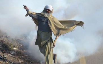 TOPSHOT - A Pakistani protester of the Tehreek-i-Labaik Yah Rasool Allah Pakistan (TLYRAP) religious group throws a tear gas shell back towards police during a clash in Islamabad on November 25, 2017. (Photo: AAMIR QURESHI/AFP/Getty Images)