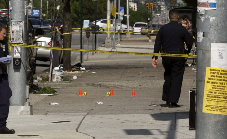 Police place evidence markers at spots where shell casings have been found at the scene of a shooting at the intersection of West North Avenue and Druid Hill Avenue in West Baltimore, Maryland May 30, 2015. Local media have reported more than 35 murders in the city of Baltimore since the April rioting over the death of 25-year-old resident Freddie Gray and shootings continue regularly in his West Baltimore neighborhood. REUTERS/Jim Bourg