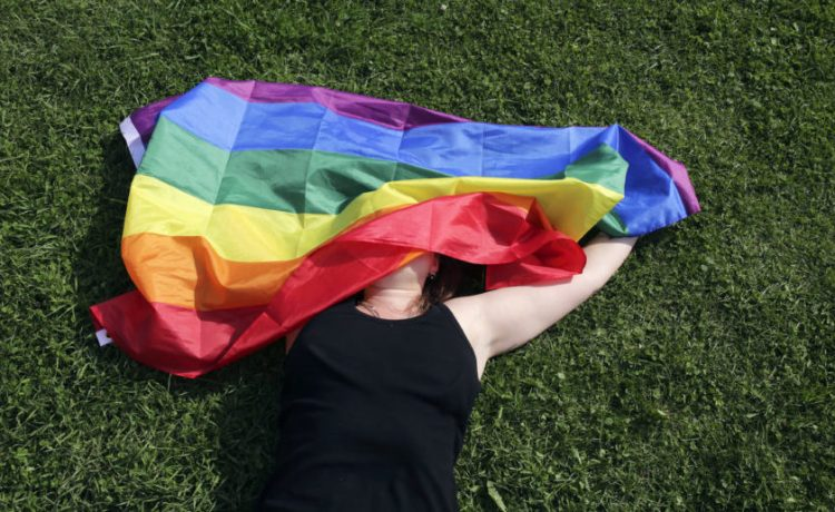 """A woman with a rainbow flag lays on grass during the LGBT (lesbian, gay, bisexual, and transgender) community rally """"VIII St.Petersburg Pride"""" in St. Petersburg, Russia August 12, 2017. REUTERS/Anton Vaganov"""