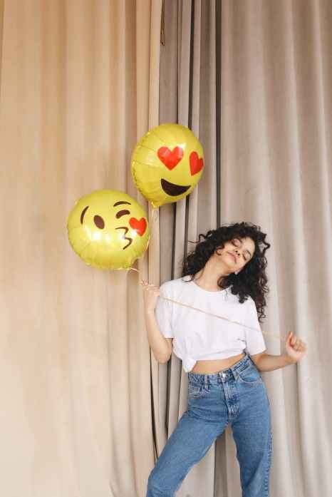 woman in white shirt and blue denim shorts holding yellow and red balloons