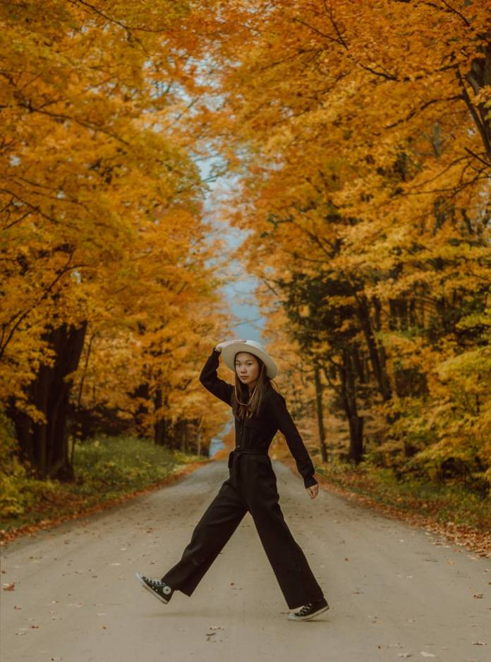 woman in black jacket and black pants walking on road between trees