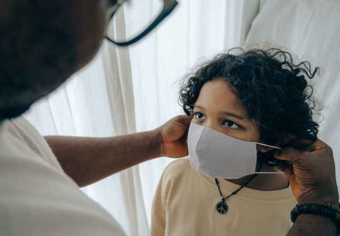 crop man putting medical mask on face of ethnic child