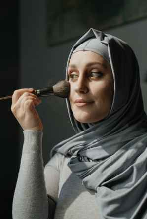 woman in gray hijab holding makeup brush
