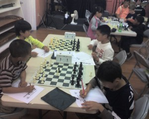 Children playing chess over the summer.