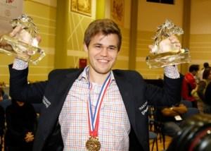 A Triumphant Magnus Carlsen holding the trophies for the Worl;d Blitz and Rapid Chess Championships. source:http://dubai2014wrb.com/en/