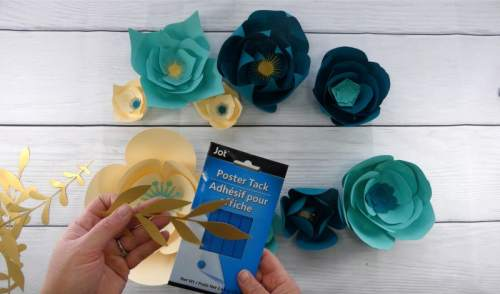 Use poster tack to hang greenery and small flowers to make a paper flower backdrop