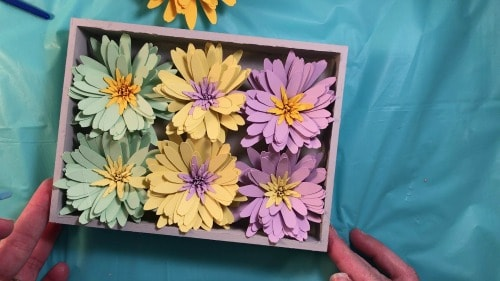 Place paper flowers inside of a shadow box for Mother's Day.