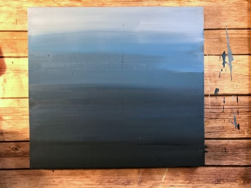 blending blue paints for an ombre painted sign