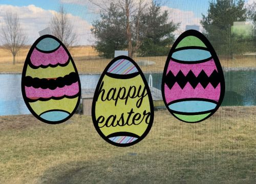 Three Easter Egg Suncatchers hanging in a window made with a Cricut cutting machine