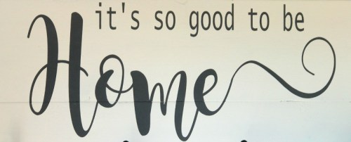 hand painted sign on farm house coat rack that says it's so good to be home