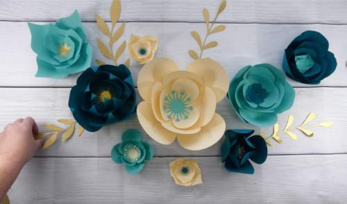 Add the greenery to finish the paper flower wall display