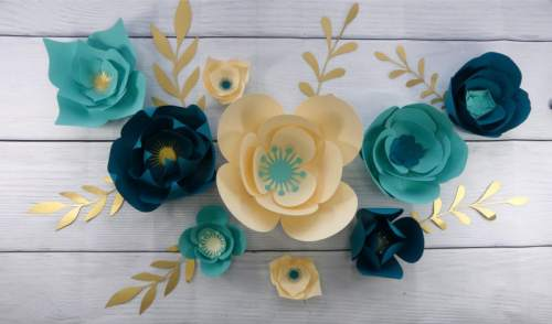 Teal and cream paper flowers used to make a DIY paper flower wall display at home