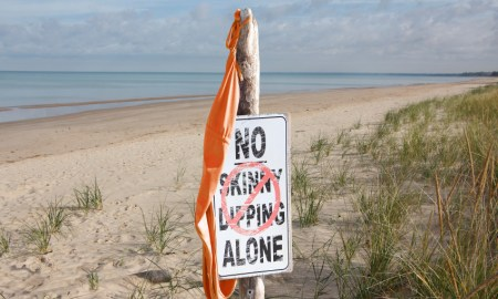 "Women's Bathing Suit Hanging From ""No Skinny Dipping Alone"" Sign at Beach"
