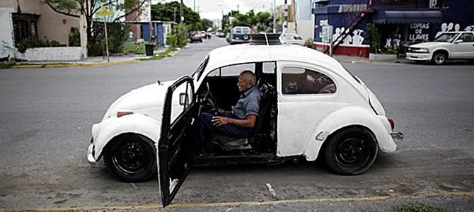 Oscar Almaguer sits in his VW Beetle 1967 in Apodaca