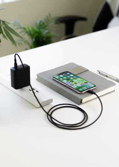recharging smartphone placed on diary on table