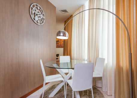 modern apartment with unusual clock on wall and glass table