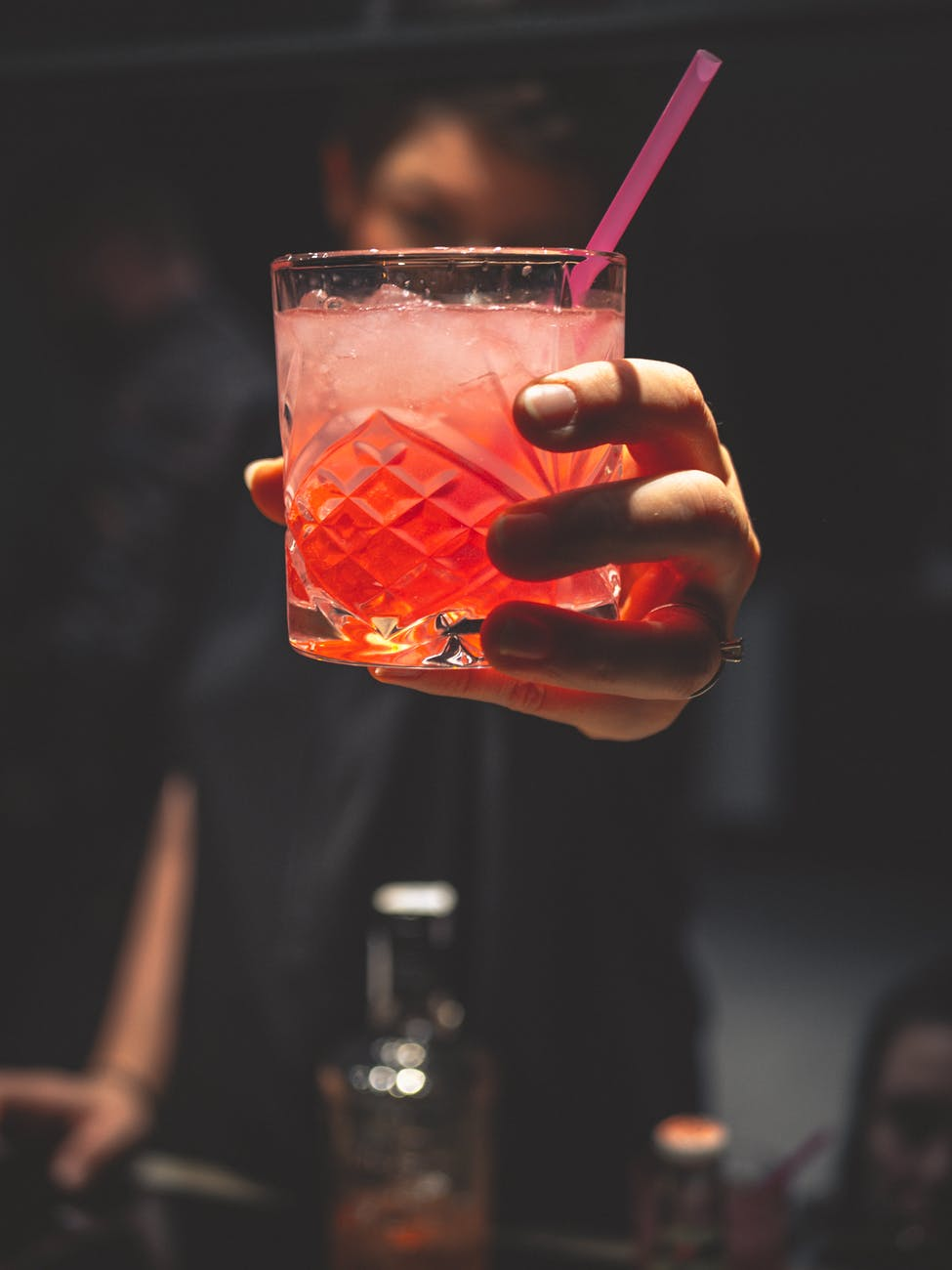 man holding forward a glass of iced pinkish colored cocktail with a straw