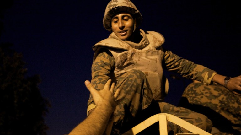 An Egyptian anti-government demonstrator extends his hand to a soldier in Tahrir Square after President Hosni Mubarak stepped down on 11 February (AFP Photo / Marco Longari)