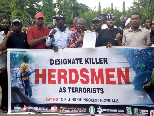Charlyboy (middle) flanked by members of the #OurMumuDonDo movement on a peaceful protest to the Federal Ministry of Justice on Monday.