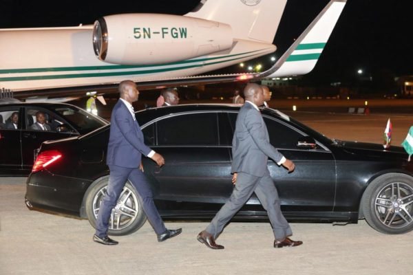 Presidential guards provide cover as President Muhammadu Buhari enters his car on May 3, 2018