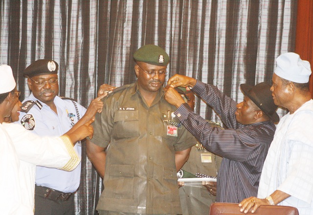 Moses Jitoboh being decorated by President Jonathan, assisted by the IGP Ringim and minister of Police Affairs Adamu Maina Waziri.
