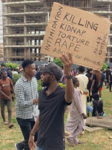 Activist Gimba Kakanda holding out a placard during #EndSARS protest in Abuja