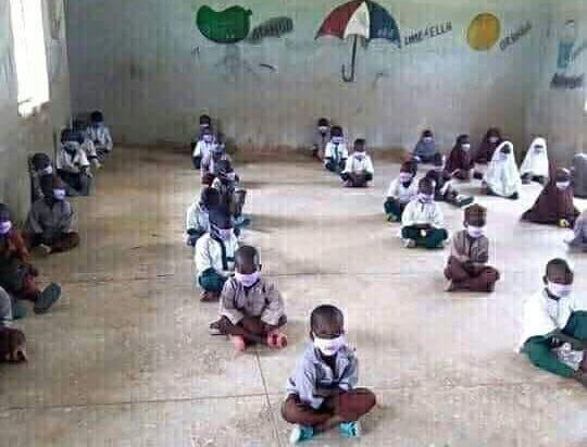 Pupils in an undisclosed school wearing face masks and sitting on a bare floor