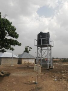 A water project with Rakiya's family house at the background at Dorawar Mallam Tanko hamlet in Jere
