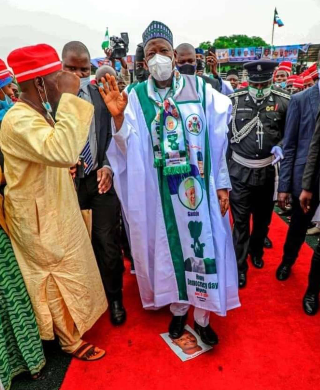 Ganduje steps on Kwankwaso's picture at a political rally