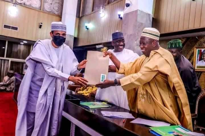 FILE PHOTO: Governor Abdullahi Ganduje (right) handing over a document to his commissioner for Local Governments, Murtala Sule Garo.