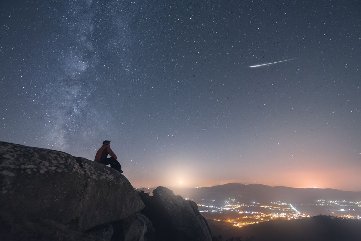 A person sits on a hillside looking at the Milky Way. Getty Images